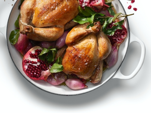 Small alternative cooked bird with pomegranate in pot.